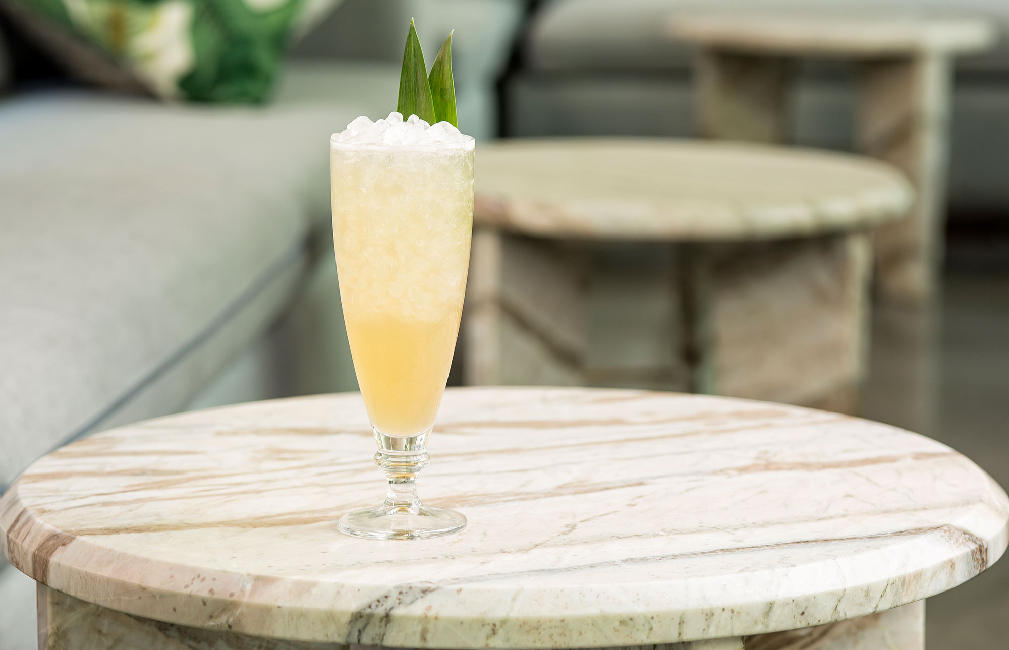 Individual Pisco Punch on an outdoor table with lounge style seating in the background