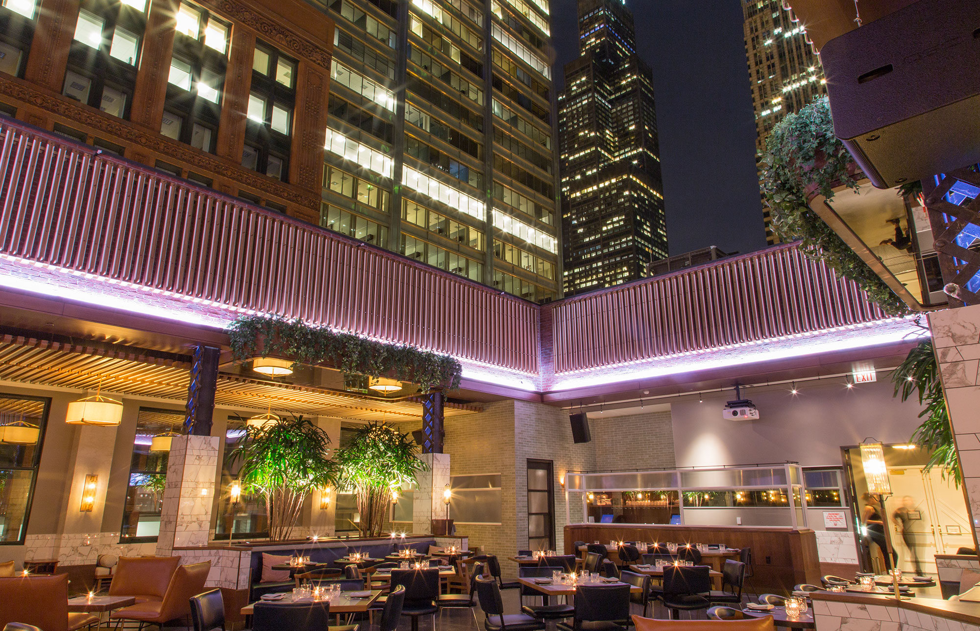 Boleo Rooftop bar with retractable roof open and 10 tables and chairs